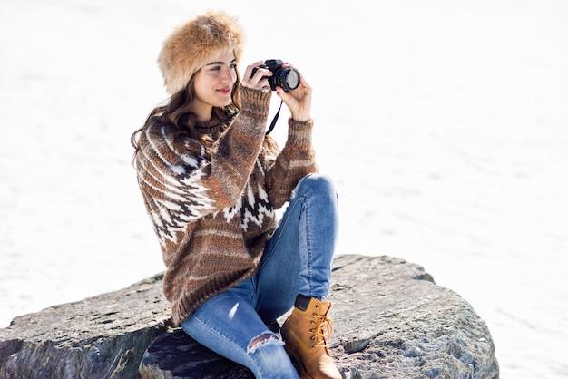 Junge frau, die fotos in den schneebedeckten bergen macht