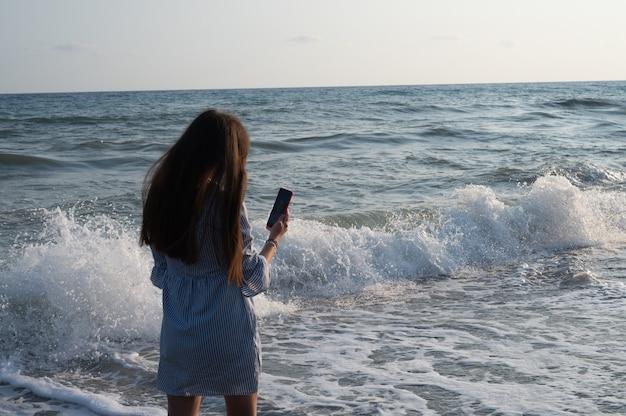 Junge frau, die fotos von sich vor dem hintergrund des meeres macht.