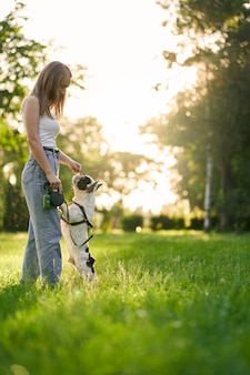Junge frau, die französische bulldogge im park ausbildet
