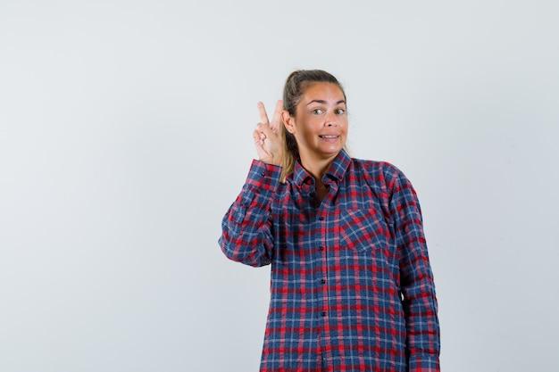 Junge frau, die friedensgeste im karierten hemd zeigt und hübsch aussieht