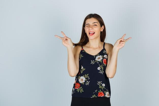 Junge frau, die friedensgeste zeigt, während sie die zunge herausstreckt, in bluse, rock blinkt und glücklich aussieht. vorderansicht.