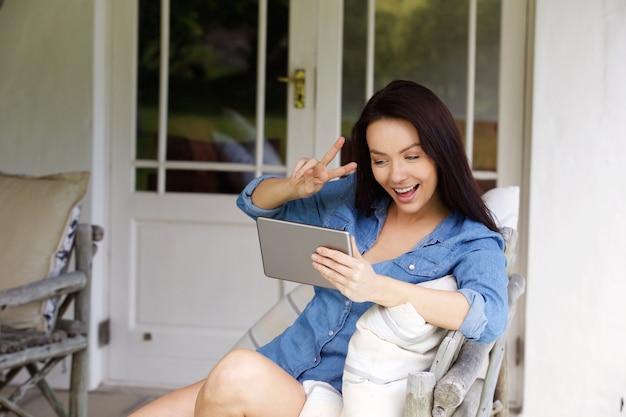 Junge frau, die friedenshandzeichen mit chatvideo macht