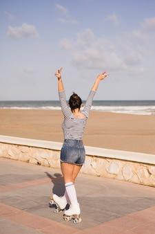 Junge frau, die friedenszeichen gestikulieren lässt, auf den seitenweg nahe dem strand zu gehen
