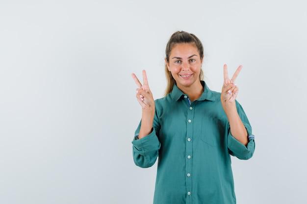 Junge frau, die friedenszeichen mit beiden händen in der grünen bluse zeigt und niedlich schaut