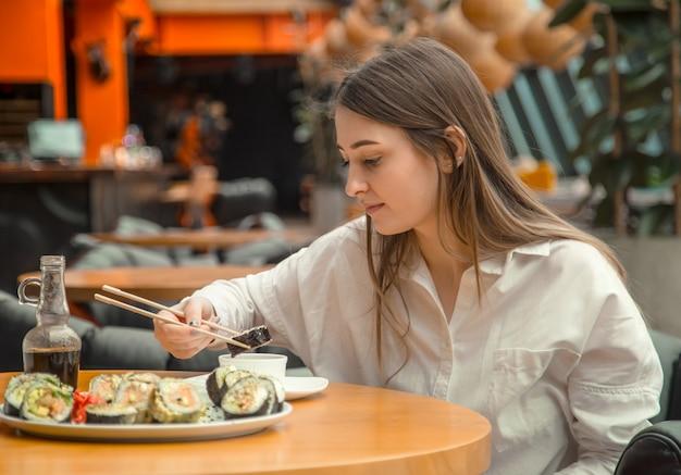 Junge frau, die frisches sushi isst und genießt