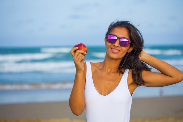 Junge frau, die frucht auf dem strand isst