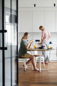 Junge frau, die frühstück hat und smartphone verwendet, während ihr mann kocht