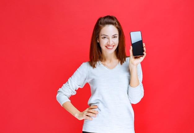 Junge frau, die für das neue modell einer smartphone-marke wirbt
