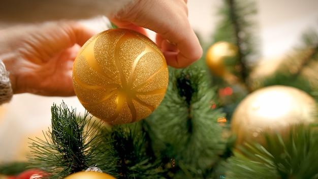 Junge frau, die funkelnde goldene weihnachtskugel hält und an einem ast hängt