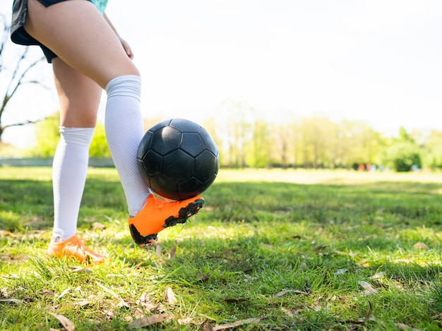 Junge frau, die fußballfähigkeiten mit ball übt