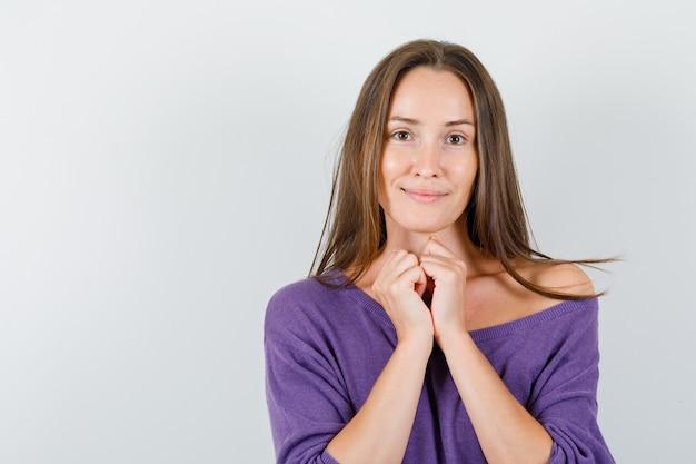 Junge frau, die gefaltete hände im violetten hemd zusammenhält und geliebt schaut. vorderansicht.