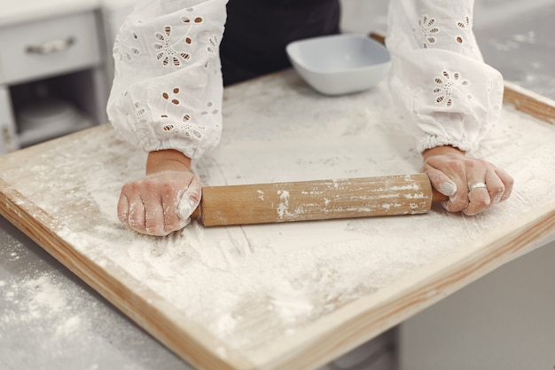 Junge frau, die geformte kekse macht