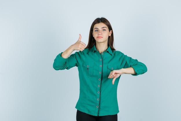 Junge frau, die gegenüberliegende daumen zeigt, die lippen im grünen hemd krümmt und unentschlossen aussieht. vorderansicht.