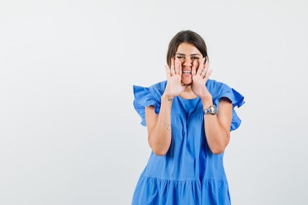 Junge frau, die geheimnis mit händen nahe mund im blauen kleid erzählt und fröhlich schaut