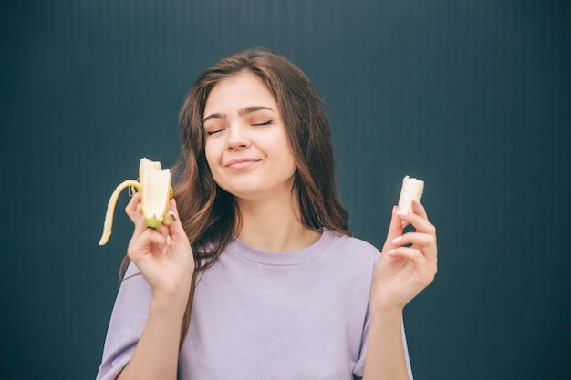 Junge frau, die gelbe reife banane genießt