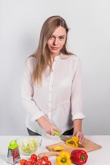 Junge Frau, die gelben Pfeffer auf hölzernem Brett schneidet