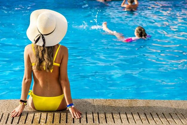 Junge frau, die gelben strohhut trägt, der nahe schwimmbad mit klarem blauem wasser am sonnigen sommertag ruht.
