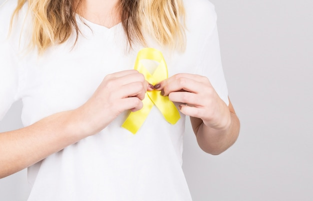 Junge frau, die gelbgoldband-bewusstseins-symbol für endometriose, selbstmordprävention, sarkomknochenkrebs, blasenkrebs, leberkrebs und krebs im kindesalter hält