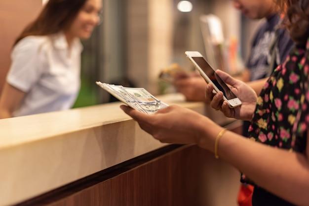 Junge frau, die geld hält und mobilen smartphone mit online-buchungsflug oder -hotel des knopfes verwendet.