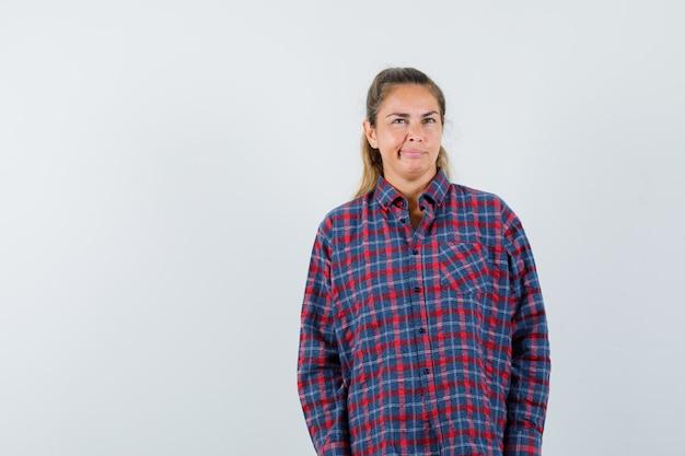Junge frau, die gerade steht, verzieht das gesicht und posiert vorne im karierten hemd und sieht hübsch aus