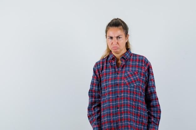 Junge frau, die gerade steht, verzieht das gesicht und posiert vorne im karierten hemd und sieht missfallen aus