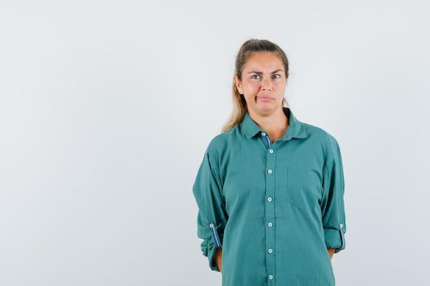 Junge frau, die gerade steht, verzieht das gesicht und posiert vorne in der grünen bluse und sieht nachdenklich aus