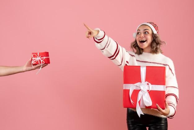 Junge frau, die geschenk hält und geschenk vom mann auf rosa annimmt