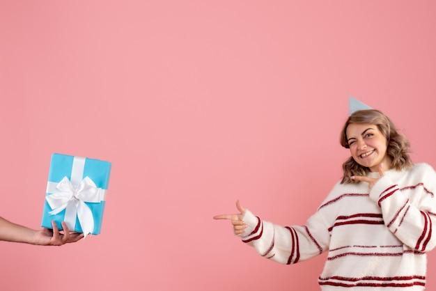 Junge frau, die geschenk vom mann auf rosa annimmt