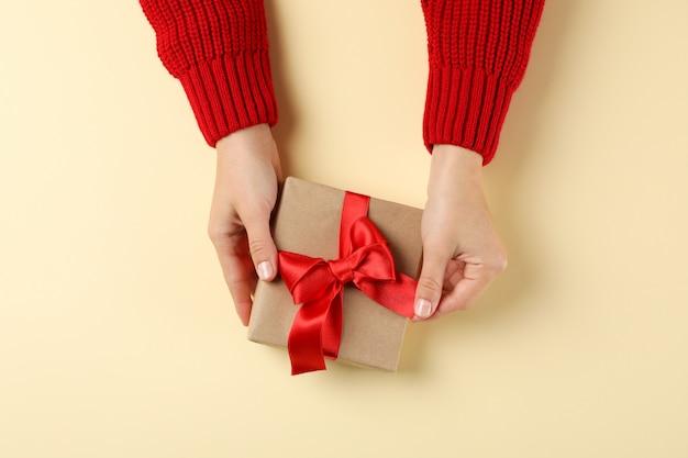 Junge frau, die geschenkbox auf farbhintergrund, raum für text hält