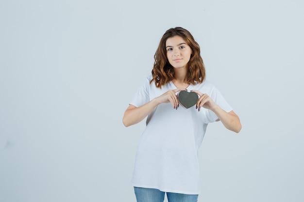 Junge frau, die geschenkbox in weißem t-shirt, jeans hält und selbstbewusst, vorderansicht schaut.