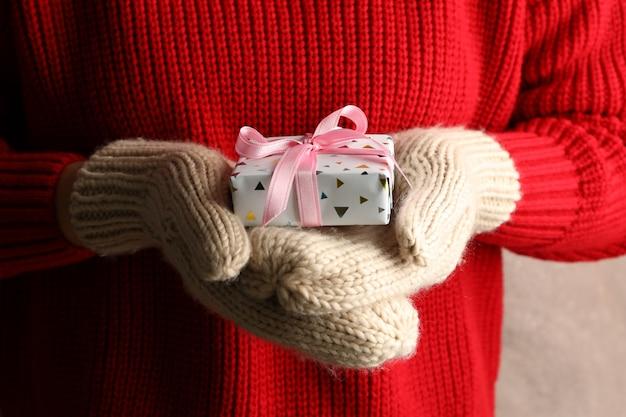 Junge frau, die geschenkbox mit rosa schleife, nahaufnahme hält