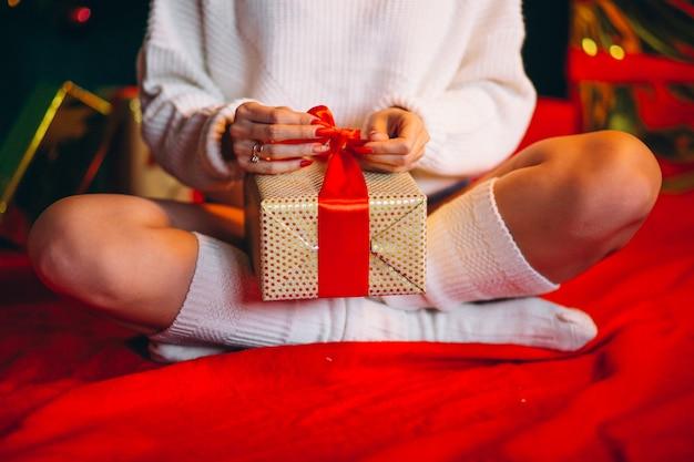 Junge frau, die geschenke durch weihnachtsbaum auspackt