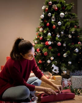 Junge frau, die geschenke für weihnachtsnacht einwickelt