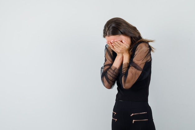 Junge frau, die gesicht mit beiden händen in der schwarzen bluse und in der schwarzen hose bedeckt und gestresst aussieht