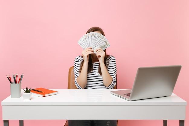 Junge frau, die gesicht mit bündel viel dollar bedeckt, bargeld, das im büro am weißen schreibtisch mit pc-laptop arbeitet