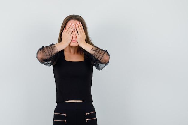 Junge frau, die gesicht mit händen in der schwarzen bluse und in der schwarzen hose bedeckt und gestresst aussieht. vorderansicht.
