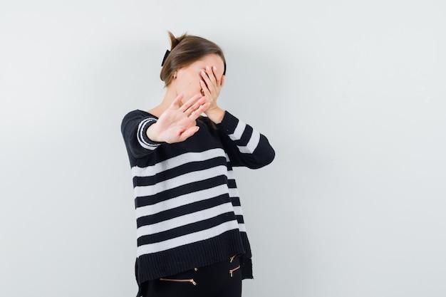Junge frau, die gesicht mit hand bedeckt und stoppschild in gestreiften strickwaren und in schwarzen hosen zeigt und genervt aussieht