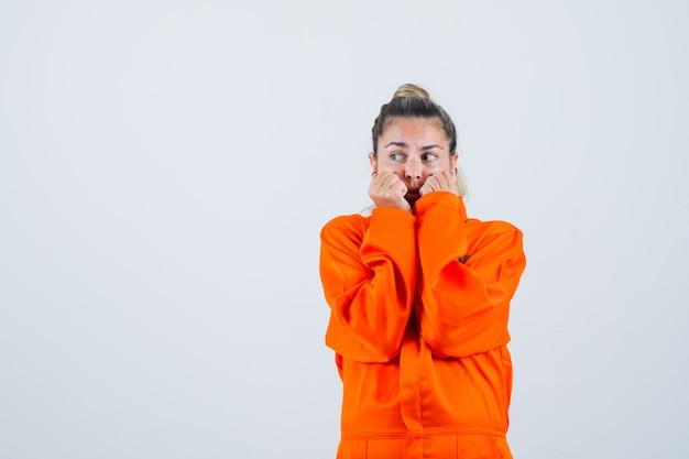 Junge frau, die gesicht mit ihren fäusten in arbeiteruniform umklammert und besorgt aussieht. vorderansicht.