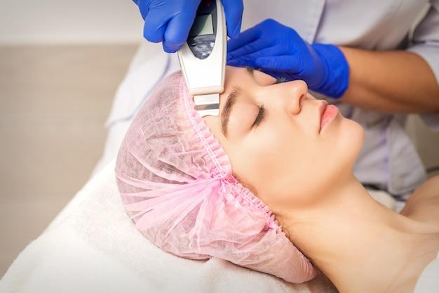 Junge frau, die gesichtshautreinigung durch ultraschallkosmetikgesichtsausrüstung im medizinischen salon erhält