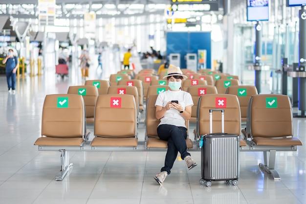 Junge frau, die gesichtsmaske trägt und mobiles smartphone im flughafen verwendet, schutz coronavirus-krankheit (covid-19) -infektion, asiatische reisende der frau, die auf stuhl sitzt. neue normale und soziale distanzierung