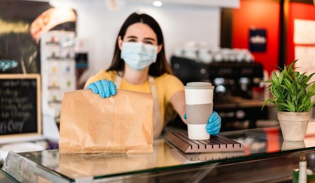 Junge frau, die gesichtsmaske trägt, während frühstück und kaffee zum mitnehmen im cafeteria-restaurant dient