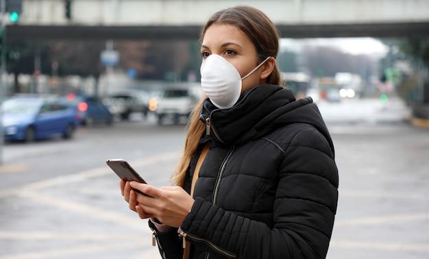 Junge frau, die gesichtsmaske unter verwendung der smartphone-app in der stadtstraße trägt