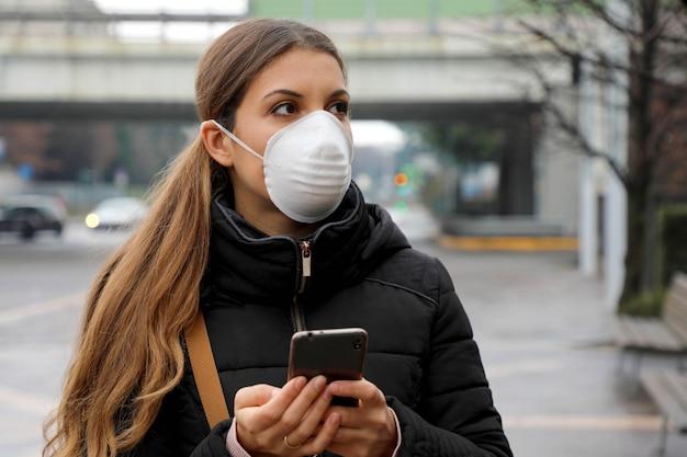 Junge frau, die gesichtsmaske unter verwendung des smartphones in der stadtstraße trägt