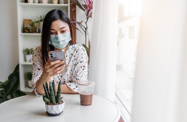 Junge frau, die gesichtsmaske zum schutz coronavirus (covid-19) trägt und smartphone im café verwendet