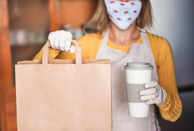 Junge frau, die gesichtswassermelonenmaske trägt, während essen zum mitnehmen und kaffee in bar-cafeteria dient