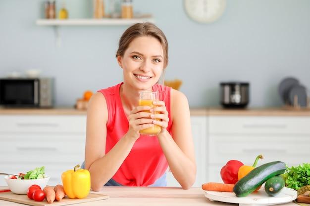 Junge frau, die gesunden saft in der küche trinkt. ernährungskonzept