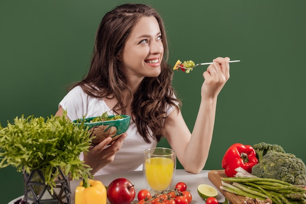 Junge frau, die gesundes essen am grünen hintergrund isst