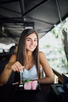 Junge frau, die gesundes essen sitzend im schönen innenraum isst