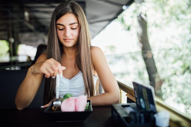 Junge frau, die gesundes essen sitzt im schönen innenraum isst