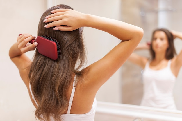 Junge frau, die gesundes haar vor einem spiegel bürstet